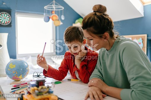 Photo of a young boy being homeschooled by his mother in his bedroom