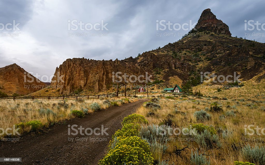 Homestead surrounded by rugged landscape, Cody, Wyoming, USA. stock photo
