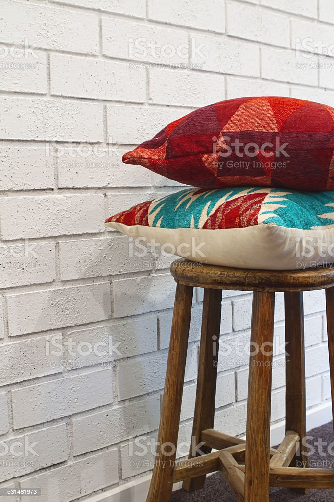 Homewares decorator cushions on a wooden stool stock photo