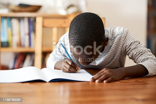 Cropped shot of a young boy doing his homework on a desk at home