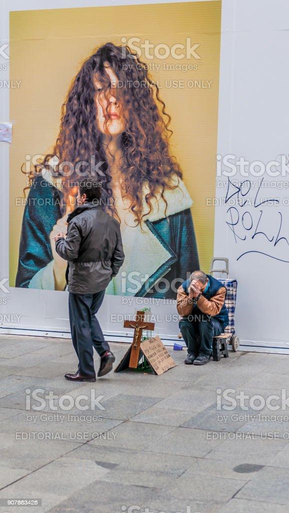 Persona de Homless llevando todas sus pertenencias en un carrito por las calles - foto de stock
