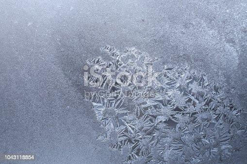 istock Homogeneous white frozen window with spot of frosty pattern of snowflakes. 1043118854