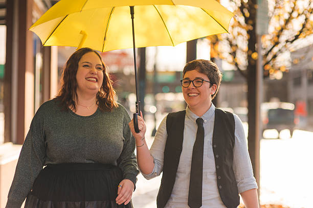 Homosexual couple spending time together and laughing in the city A lesbian couple are  walking out in the city together with an umbrella while laughing transgender stock pictures, royalty-free photos & images