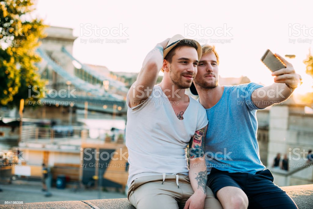 Homosexual couple taking selfie near famous bridge on Danube river royalty-free stock photo