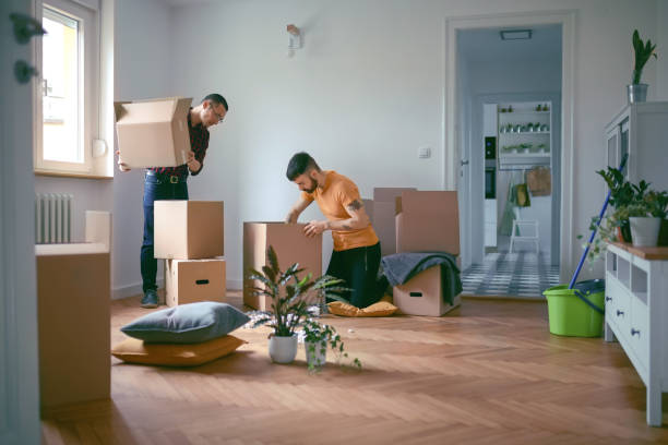 Homosexual couple unpacking boxes in a new home stock photo