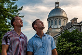 Young homosexual couple visiting the old port of Montreal at sunset.
