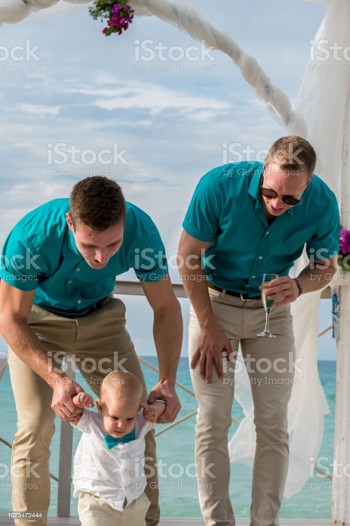 Homosexual godparents and their young nephew in a wedding celebration stock photo