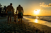 Homosexual godparents and their godchild by the beach of Varadero at sunset, Cuba.