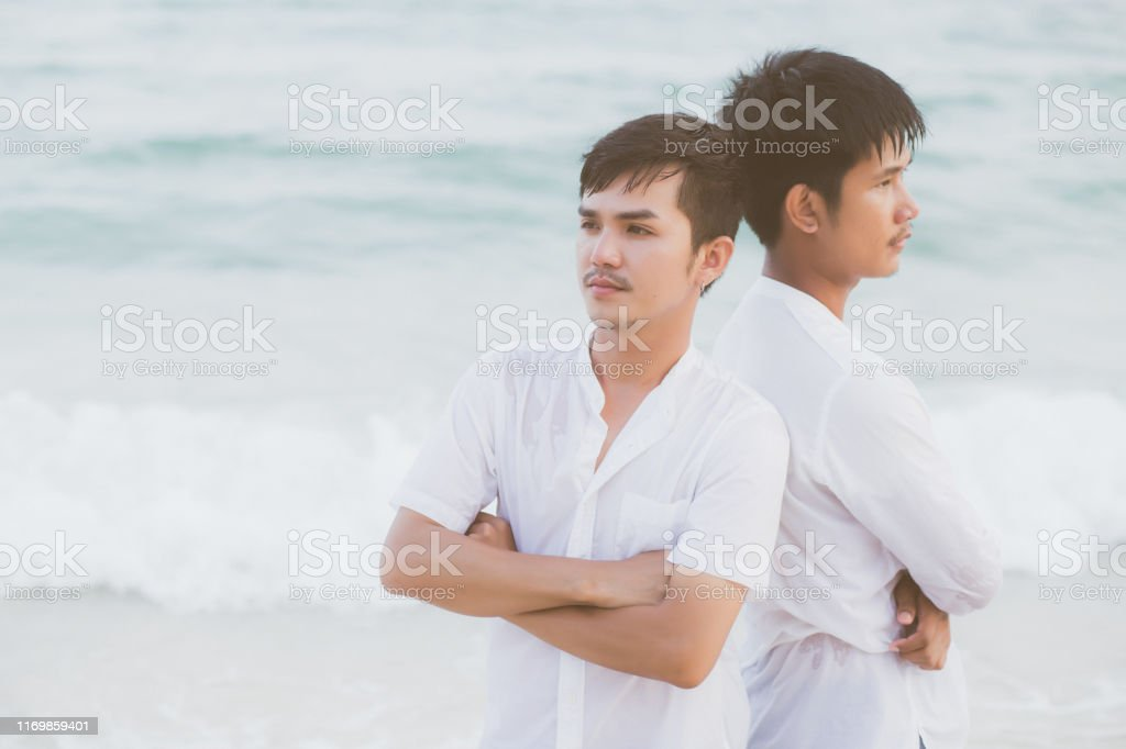 Homosexual portrait young asian couple standing problem on beach in...