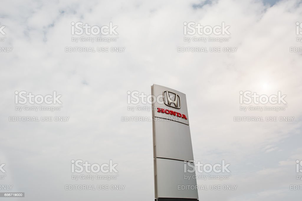 Kiev, Ukraine - March 22, 2017: Honda logo against sky near car selling and service center. stock photo