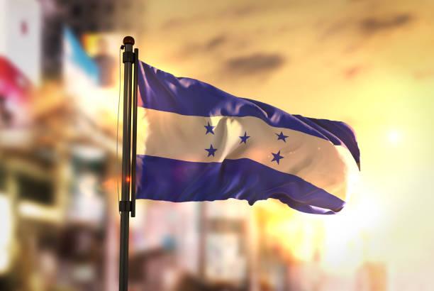 bandera de honduras contra la ciudad borrosa de fondo en contraluz amanecer - bandera de honduras fotografías e imágenes de stock