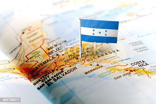 The flag of Honduras pinned on the map. Horizontal orientation. Macro photography.
