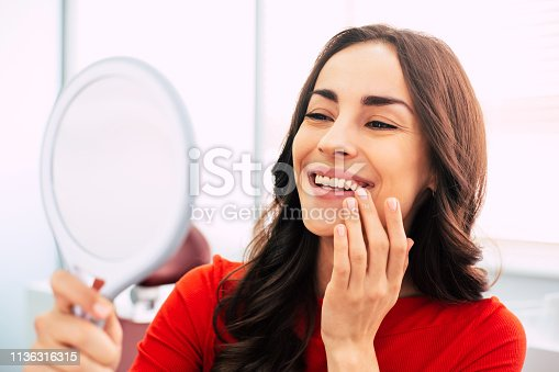 istock Honed to perfection. Fabulous woman clothed in red sweater, with curly long hair and elegant hands is holding a mirror for looking through the final work of dental doctor. 1136316315
