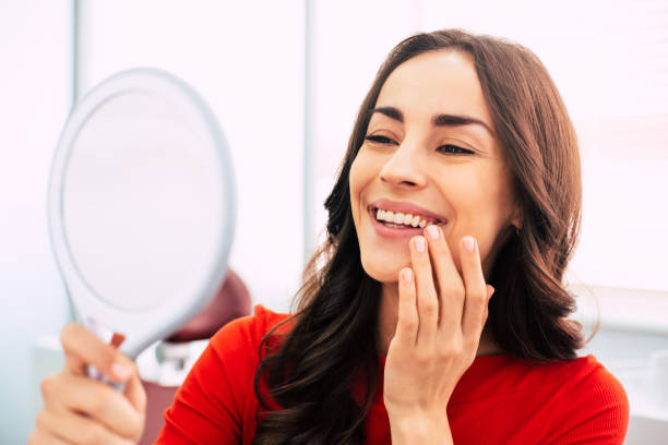 honed to perfection. fabulous woman clothed in red sweater, with curly long hair and elegant hands is holding a mirror for looking through the final work of dental doctor. - dental implants stock photos and pictures