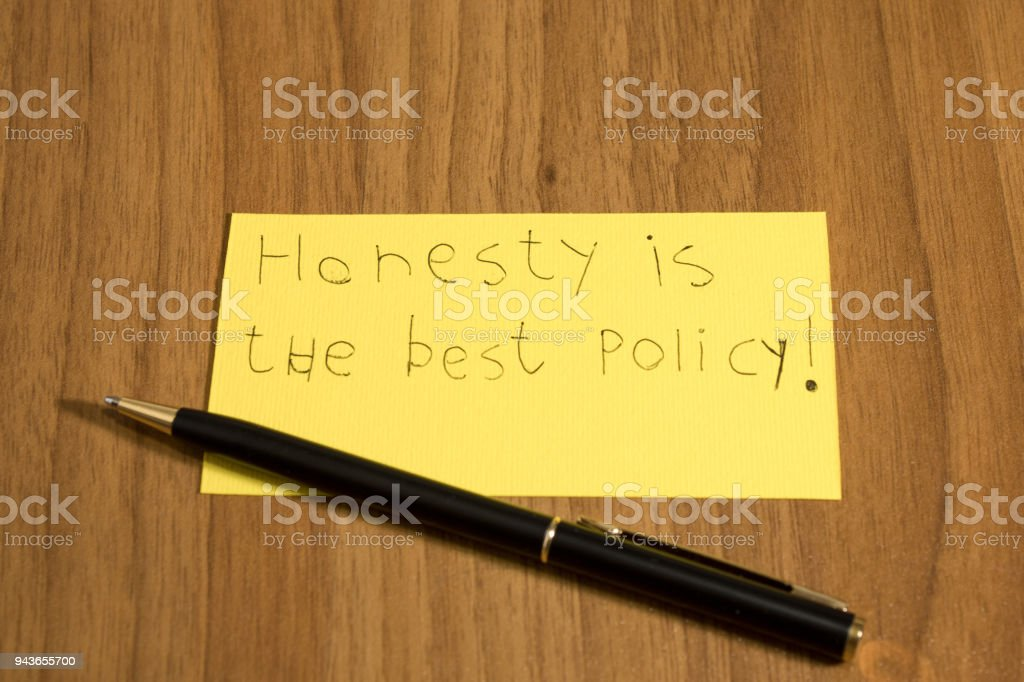 Honesty is the best policy handwrite on a yellow paper with a pen composition stock photo