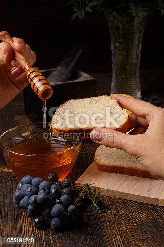 The liquid honey flows from the honey stick on a slice of bread. Organic food. Sweet dessert made from natural products.
