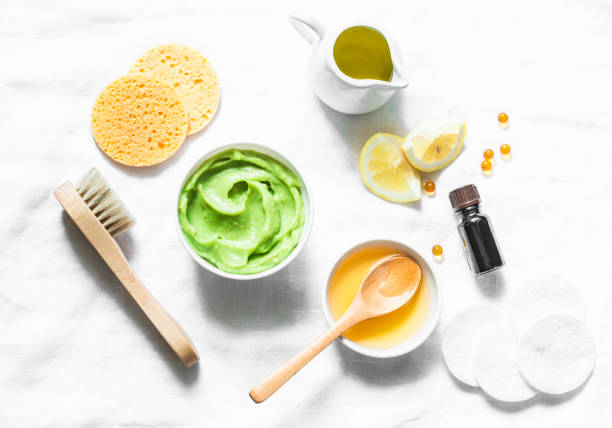 Honey and avocado face mask on light background, top view. Beauty, youth, skin care concept. Flat lay stock photo