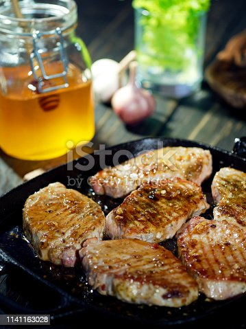 Homemade pork chops with honey and garlic glaze just brought onto the table in the frying pan
