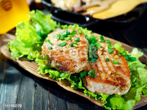 Homemade grilled pork chops with honey and garlic glaze just served on the wooden plate