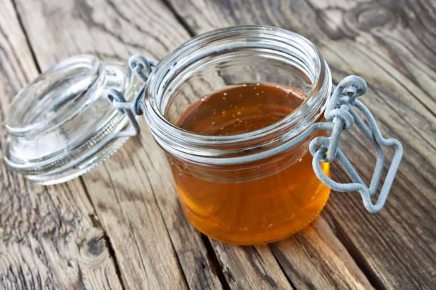 Honig und Glas vor Holzrücken – Foto