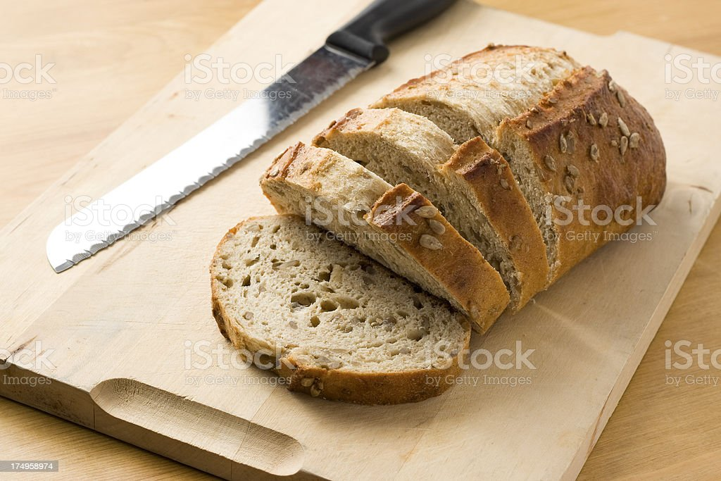 Honey and seed loaf of bread on a chopping board stock photo