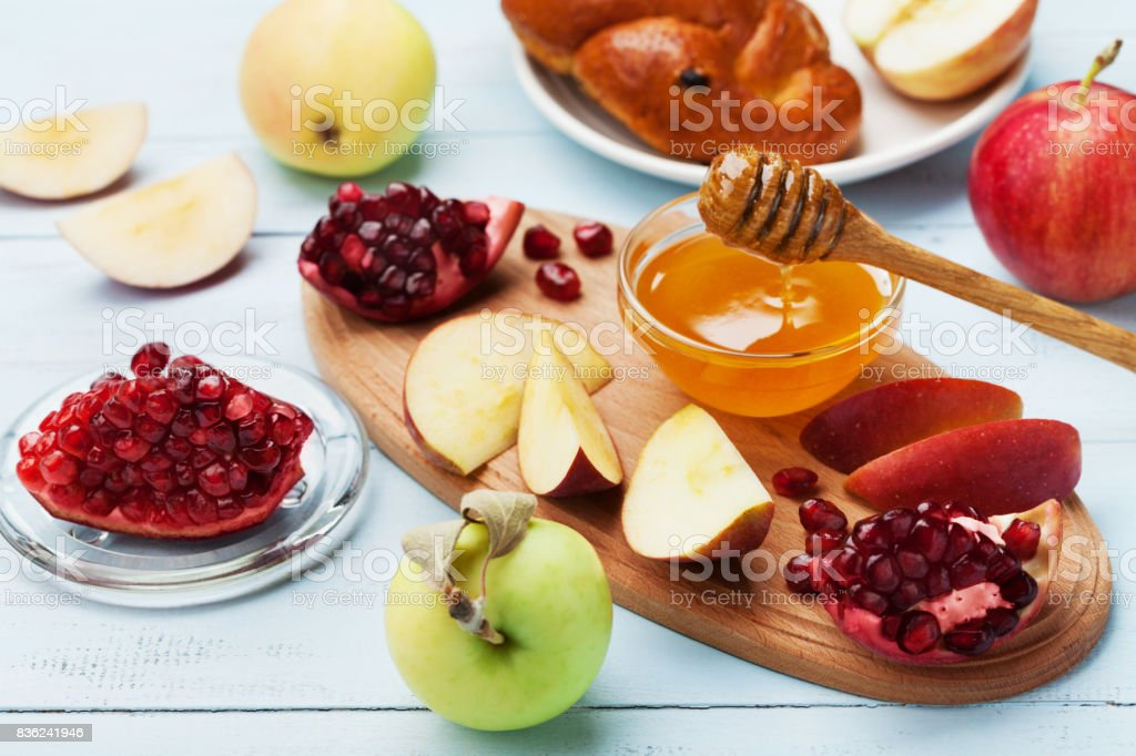 Honey, apple slices, pomegranate and hala. Table set with traditional food for Jewish New Year Holiday, Rosh Hashana. stock photo