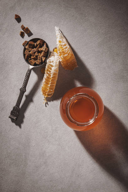 Honey background. Honey in a glass jar, honeycomb and propolis in an iron spoon. Light gray background. stock photo