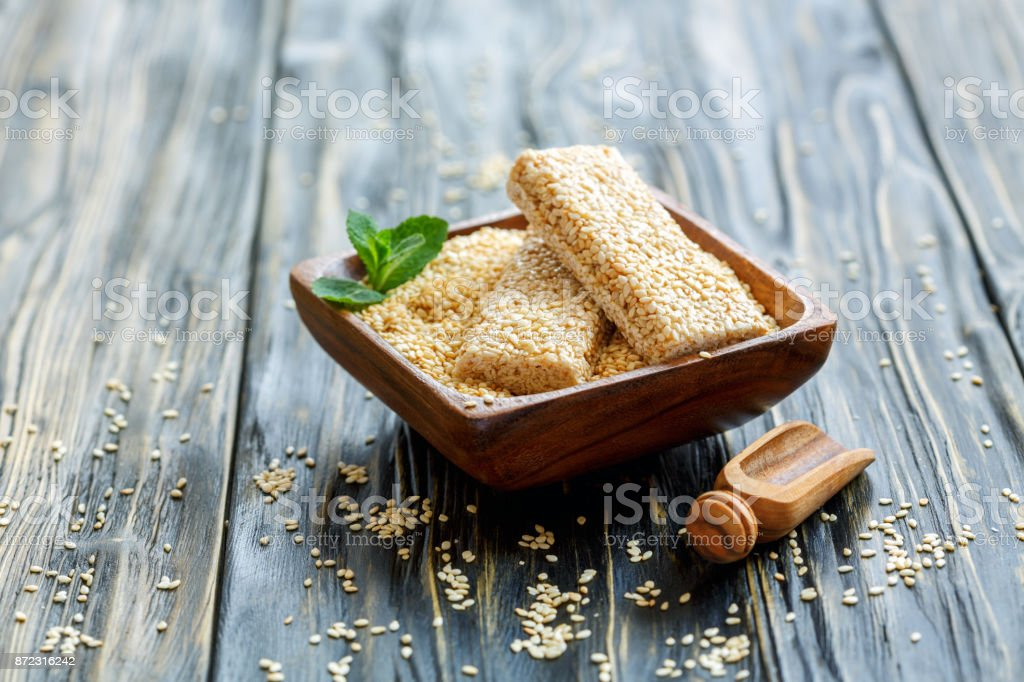 Honey bars in a wooden bowl with sesame seeds. stock photo