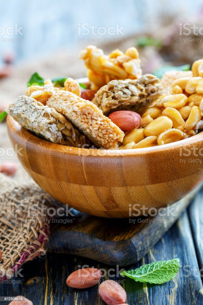 Honey bars with peanuts, sesame seeds and sunflower seeds in a wooden bowl closeup. stock photo
