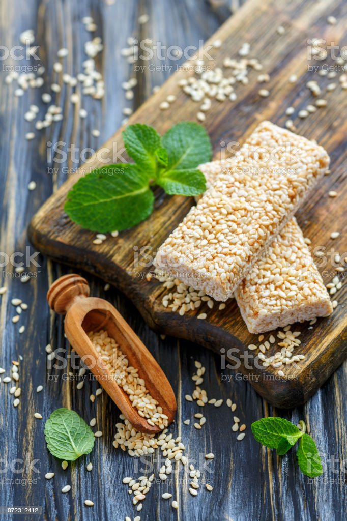 Honey bars with sesame seeds and wooden scoop. stock photo