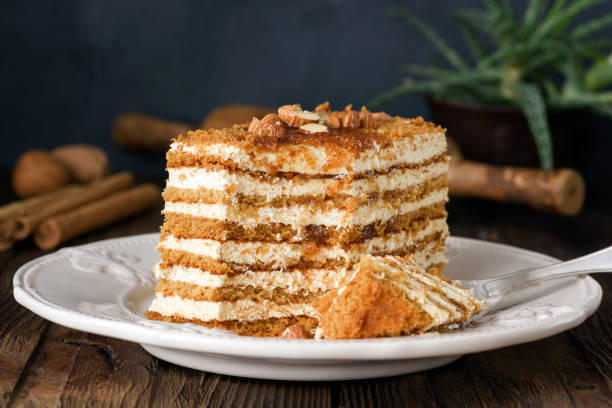 Honey cake with almonds on white plate Honey cake with almonds on white plate. Russian cake Medovik biscuit stock pictures, royalty-free photos & images