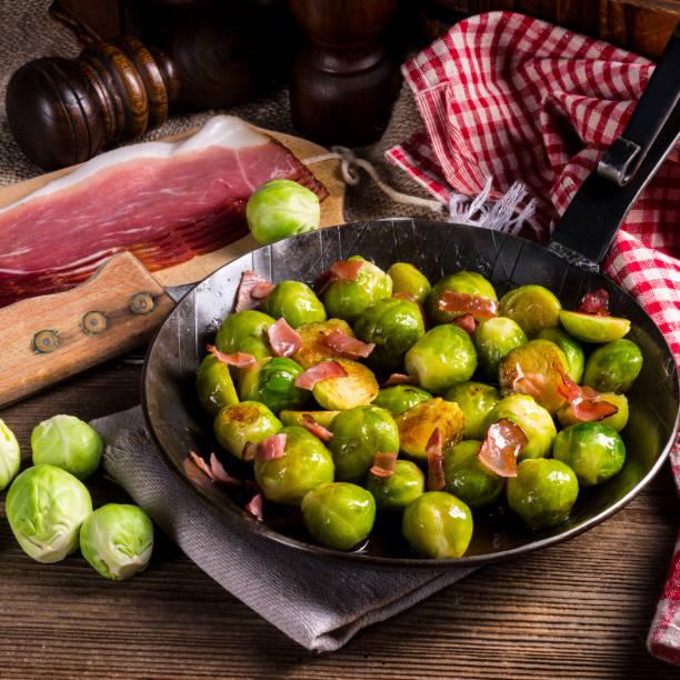 honig karamellisiert, rosenkohl mit schinken - silberzwiebeln stock-fotos und bilder