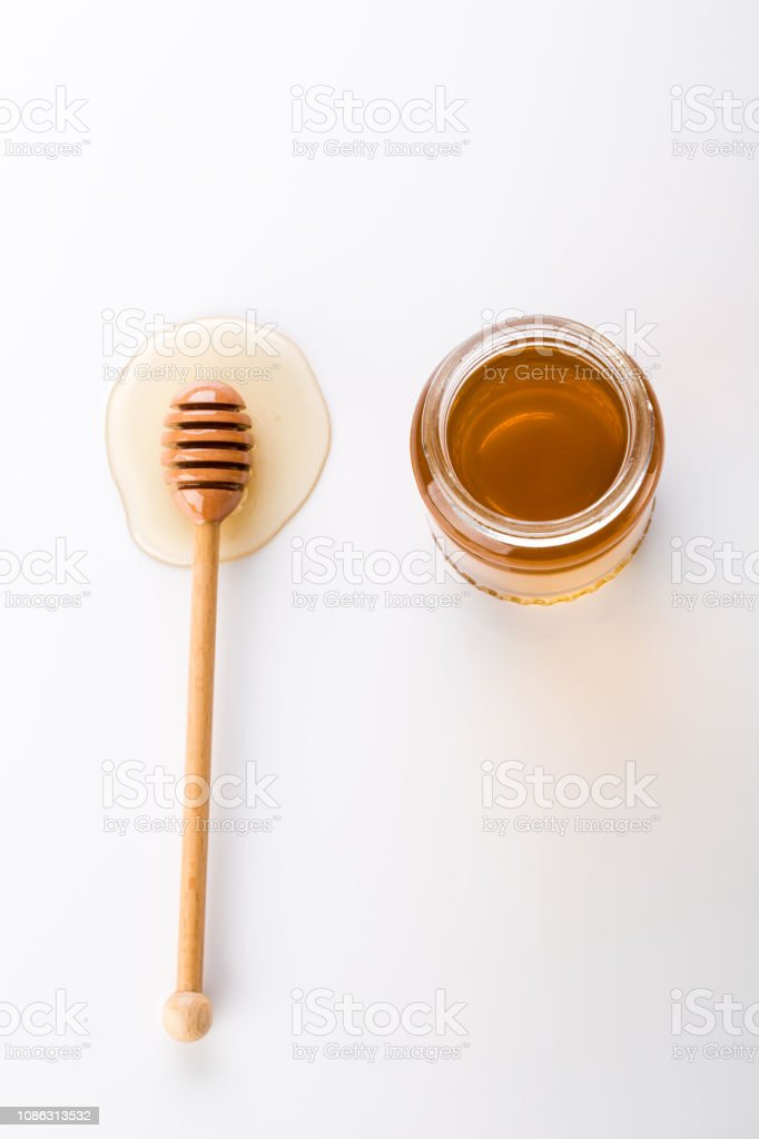 Honey dipper and honey in jar on white background. stock photo