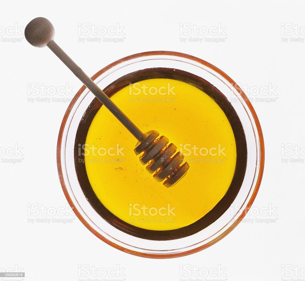 Honey dipper in bowl of honey stock photo