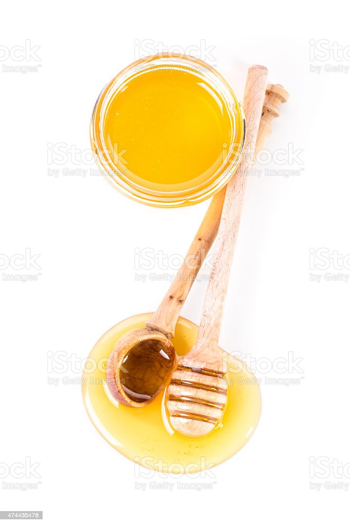 Honey dipper on the bee honeycomb background. stock photo