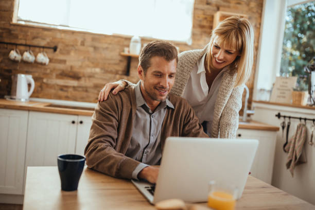 Honey, do you need help? Man working online and his wife is helping him electronic banking stock pictures, royalty-free photos & images