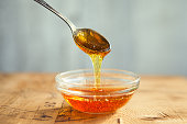 istock Honey dripping from spoon in the cup 1221869380