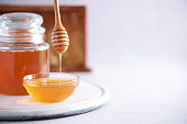 istock Honey dripping from wooden honey spoon in jar on grey background. Copy space. Autumn harvest concept. 1176623881