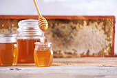 istock Honey dripping from wooden honey spoon in jar on grey background. Copy space. Autumn harvest concept. Banner 1176624104
