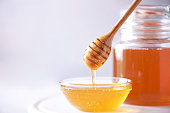 istock Honey dripping from wooden honey spoon in jar on grey background. Copy space. Autumn harvest concept. 1176629898