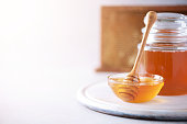 istock Honey dripping from wooden honey spoon in jar on grey background. Copy space. Autumn harvest concept. 1176629900
