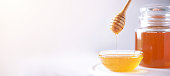 istock Honey dripping from wooden honey spoon in jar on grey background. Copy space. Autumn harvest concept. Banner 1176629914