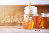 istock Honey dripping from wooden honey spoon in jar on grey background. Copy space. Autumn harvest concept. 1176629976