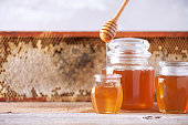 istock Honey dripping from wooden honey spoon in jar on grey background. Copy space. Autumn harvest concept. Banner 1176630120