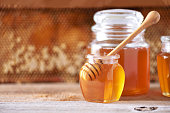 istock Honey dripping from wooden honey spoon in jar on grey background. Copy space. Autumn harvest concept. 1176630129