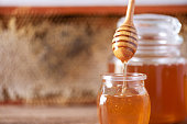 istock Honey dripping from wooden honey spoon in jar on grey background. Copy space. Autumn harvest concept. Banner 1176630144