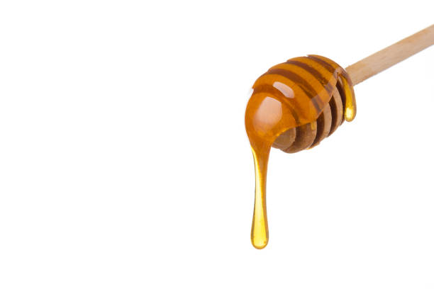 honey dripping from wooden honey spoon - miele dolci foto e immagini stock