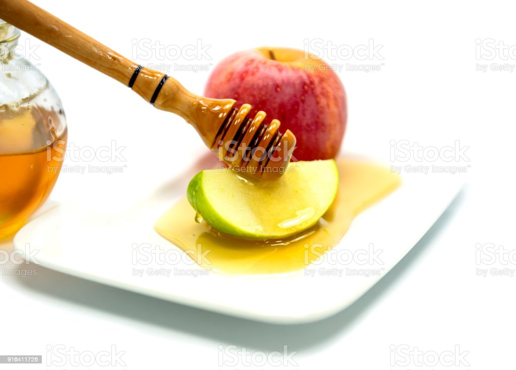 Honey dripping from wooden stick on green apple slices isolated on white stock photo