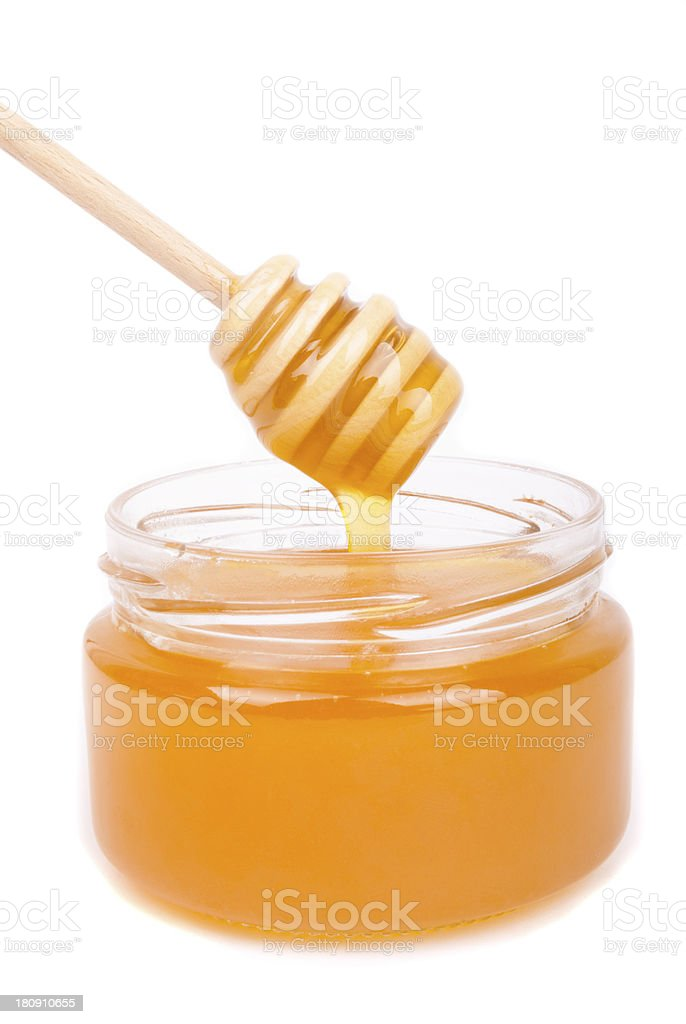 Honey dripping into a jar with special spoon. royalty-free stock photo