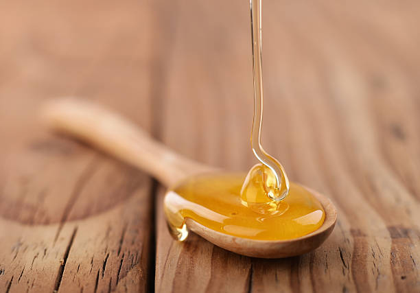 Honey dripping on a wooden spoon stock photo